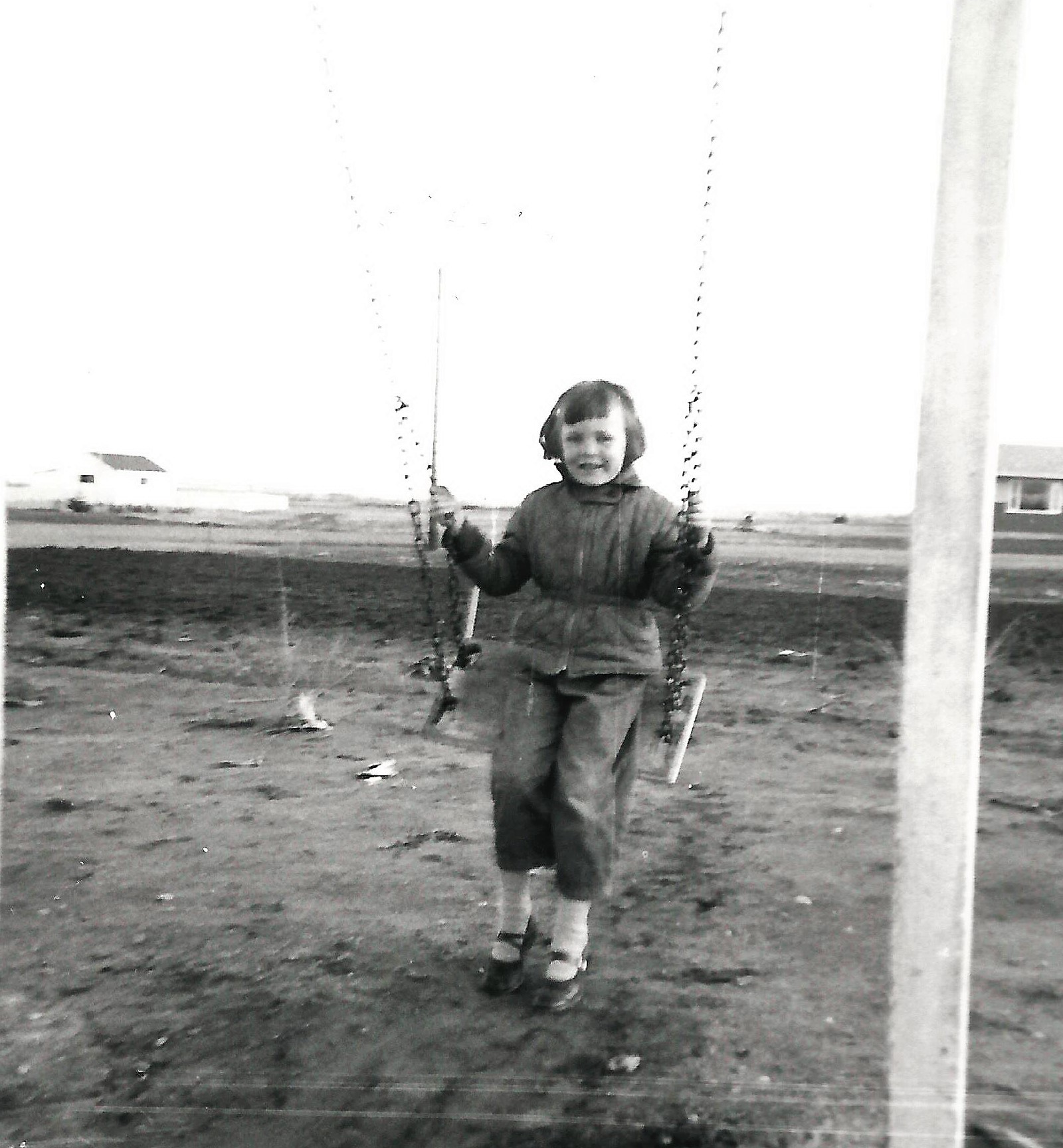 Leslie MacLachlan on baclyard swing 1956 (Wills house on right)William's garden behind Leslie and Ortona st. (2)